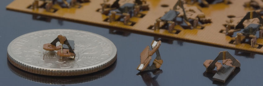 Tiny manufactured objects next to a quarter for scale