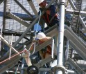 two men working in a communications tower lowering equipment with ropes