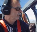 man with headset in cockpit of plane