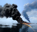 Dark clouds of smoke emerge as a controlled burn of spilled oil takes place on the ocean surface.
