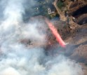 aerial view of wildfire with smaller plan below dispensing substance over flames