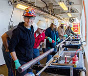 Zealandia on deck: a sediment core obtained through deep-sea drilling is pored over by scientists.