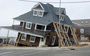 House sinking into sand by a coast
