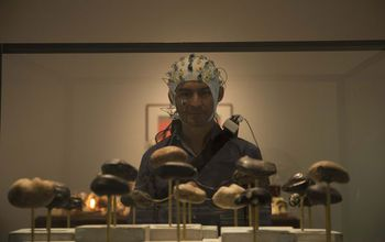 person with EEG cap looking at art