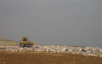 A piece of heavy equipment pushes trash in a landfill.