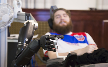 A man manipulates a robotic arm via a computer chip in his brain.