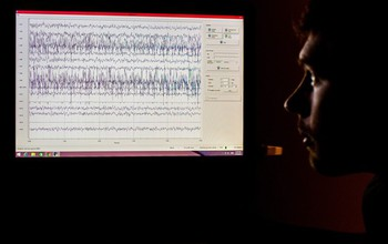 man looking at EEG data on the screen