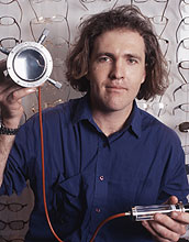 Photo of Saul Griffith with his eyeglass lens 'printer.'