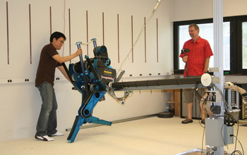 Two people and a robot with lateral support boom.