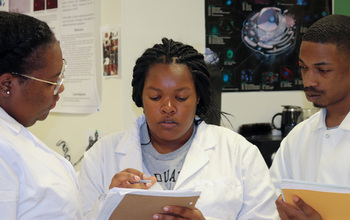 A researcher talks with two students in a laboratory settings. All are wearing lab coats.