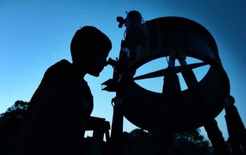 person looking through a telescope at the sky