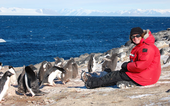 Jean Pennycook with group of Adélie penguins on the beach