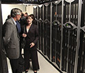 Photo of LANL Director Charles McMillan and UNM's Susan Atlas standing next to computers.