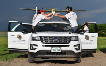 Researchers load instrumentation onto a tracker vehicle before a drone's takeoff.