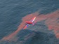 An aircraft applies dispersants over a slick of sunlight-weathered oil in the waters of the Gulf of Mexico.