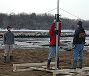 Scientists install a Sediment Elevation Tube in a salt marsh to observe the activity of microbes.