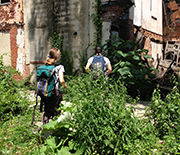 Two women researchers look for mosquito habitat and larvae near an abandoned building.