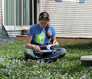 Female scientist sitting in grass, holding notepad and pencil.