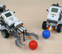Photo of robots programmed by students that are handling balls.