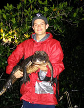 Photo of Adam Rosenblatt holding an alligator.
