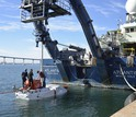 Researchers work on Alvin off the stern of the R/V Atlantis during sea trials off San Diego.