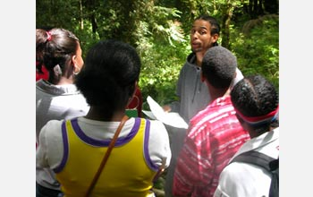 Photo of rapper C.A.U.T.I.O.N. engaging kids from Washington State exploring the forest environment.