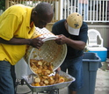 Two men dumping shrimp and corn from a food basket