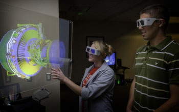 Students observe a 3-D projection of an aircraft engine