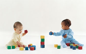 Photo of two babies playing with blocks.