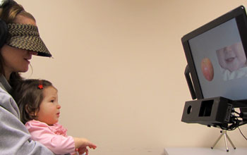Photo of a 10-month-old baby held by a woman watching images on a monitor.