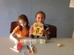 two girls with crayons, a robot and cubes