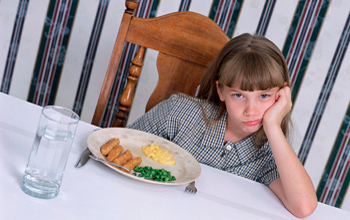 Photo of child with dinner plate before her.