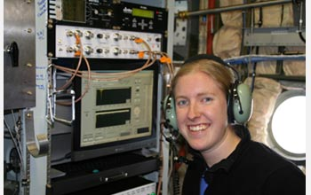 Photo of scientist Kerri Pratt inside an NSF C-130 aircraft, tracking cloud particles.