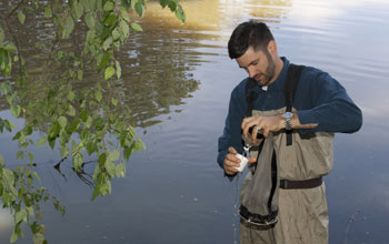 Scientist Mark Urban filters a tow net sample of zooplankton from a pond.