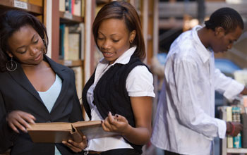 Photo of two female African American students holding an open book.