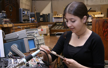 Image of a young woman holding a circuit board and next to table with electronics.