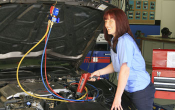 Photo of a smiling young woman working on a car engine.