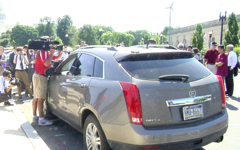 a driverless cadillac surrounded by people in front of Capitol Hill