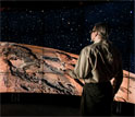 Man standing in a CAVE2 room looking at planet Mars.