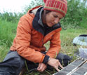 Female gradute student examines lake sediment core from southern Alaska