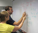 Photo of two researchers working on a problem at a white board.