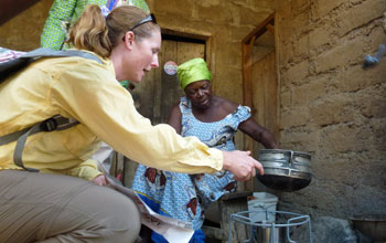 Scientist showing local Ghanian woman how to use a new cookstove.
