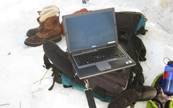 Photo of a laptop downloading data, backpack, hiking boots and instruments in the snow.
