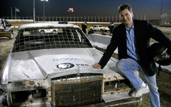 Photo of David Pogue leaning against a car with a NOVA logo on the car's hood.