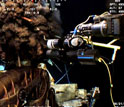 Photo of the manipulator arm of a robotic vehicle, upper right, moving sampler toward oil and gas.
