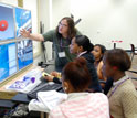 Photo of Wesley Evan showing high school students how to use Amira visualization package.