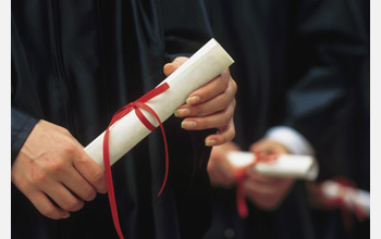 Photo of a graduate holding a diploma.