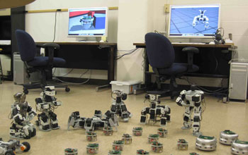 Photo of two computers and a terrestrial robot swarm