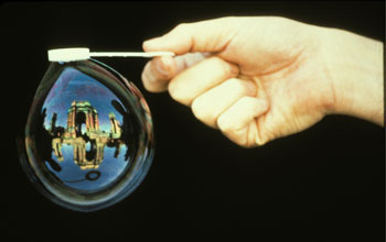 Image of a hand generating a bubble containing an image of the Exploratorium.