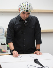 artist drawing while wearing EEG cap